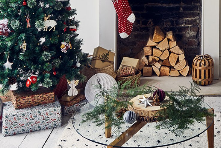 Fireplace with wooden log and red and white hanging stocking with decorated Christmas tree and wrapped gifts underneath.