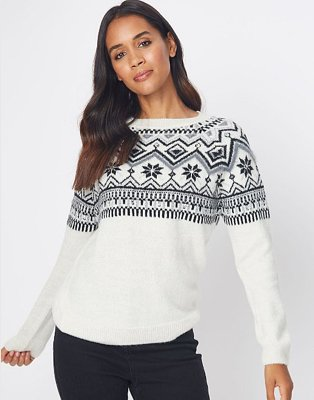 Brown haired woman poses wearing white fairisle jumper and black jeans.