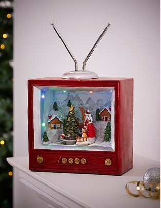 Red musical character TV decoration on white table with lit Christmas tree in background.