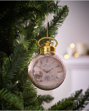 Gold glitter pocket watch Christmas tree bauble hanging from branch of Christmas tree.