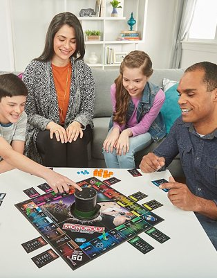 Boy, woman, girl and man gather around white table playing Monopoly Voice Banking