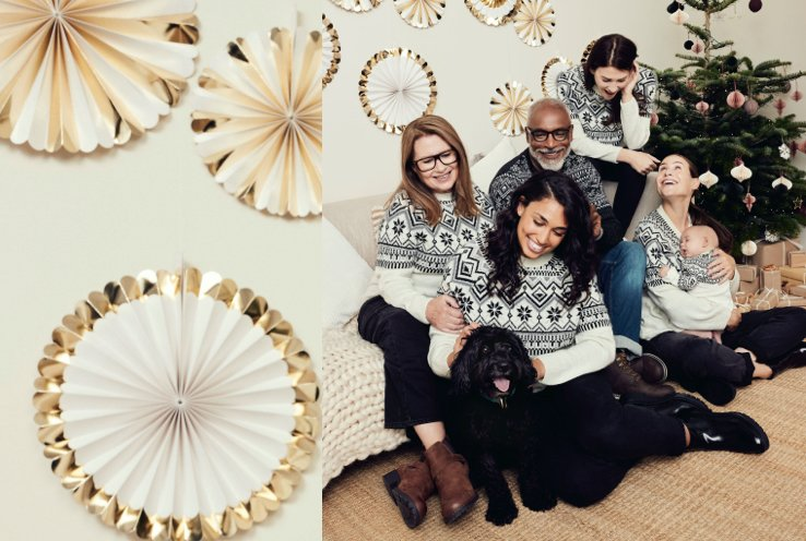 Group of four women, man, baby and dog gather together wearing cream and navy Christmas fairisle knitted jumpers with Christmas tree, presents and gold and cream decorations in the background.