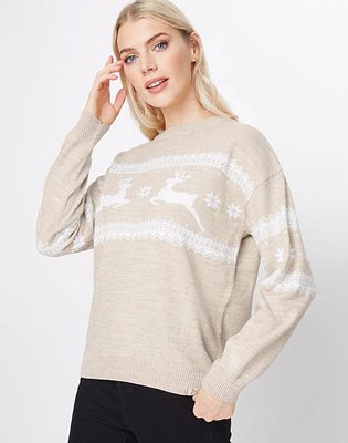 Blonde woman poses raising right hand to side of face wearing Billie Faiers fairisle reindeer matching Christmas jumper and black jeans.