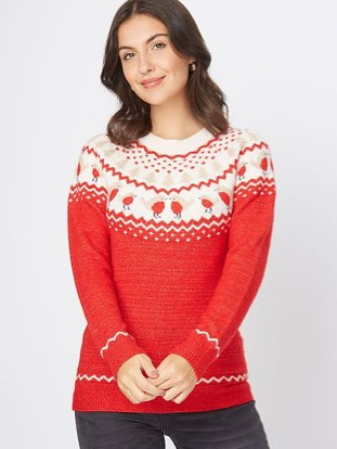 Brunette woman poses wearing red fairisle robin knitted Christmas jumper and black jeans.