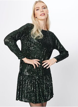 Blonde woman poses with hands on hips wearing forest green sequined tiered hem dress with tights.