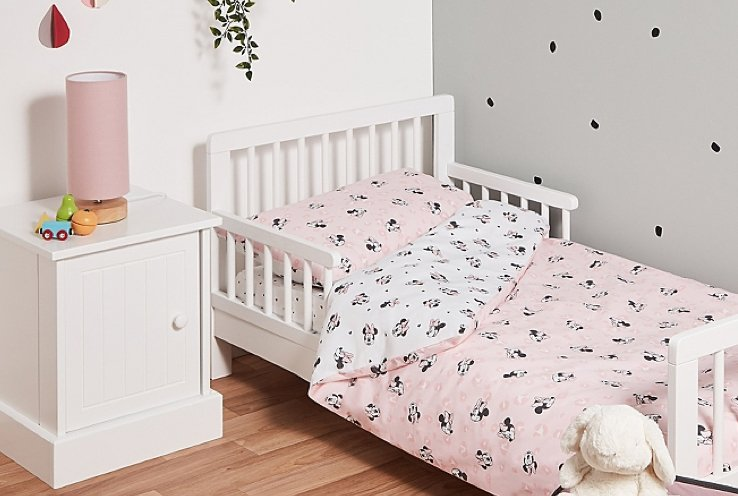 White Rafferty Toddler Bed with Disney Minnie Mouse Pink and White Patterned Duvet, White Finley Bedside Table and Pink Wooden Cylinder Lamp.