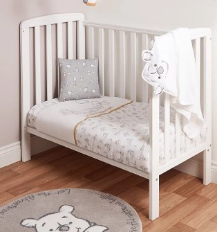White Cot Bed with White and Yellow Disney Winnie the Pooh Duvet Set, Grey Disney Winnie the Pooh Cushion and Grey Disney Winnie the Pooh Rug.