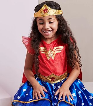 Girl poses sitting down smiling with hands on knees wearing DC Comics Wonder Woman Fancy Dress Costume.