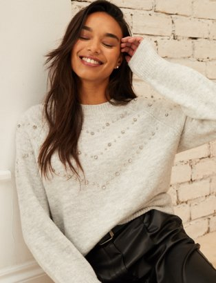 Woman with long brown hair poses smiling against a brick wall wearing a cream chevron knitted jumper and black PU trousers.