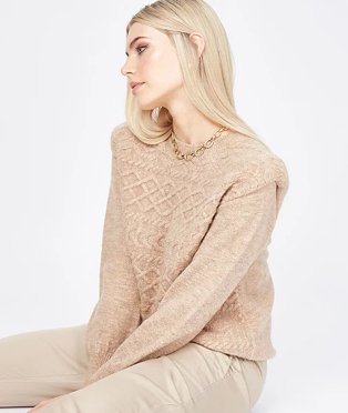 Woman with blonde hair poses sitting down wearing camel extended shoulder cable knit jumper and camel trousers.