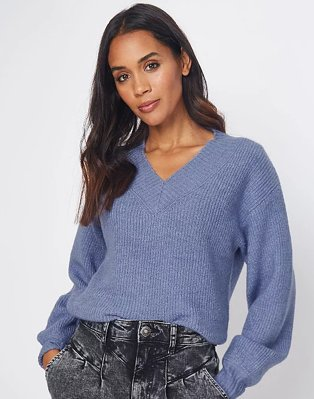 Woman with long brunette hair poses with hands in pockets wearing blue volume sleeve ribbed jumper and acid wash jeans.