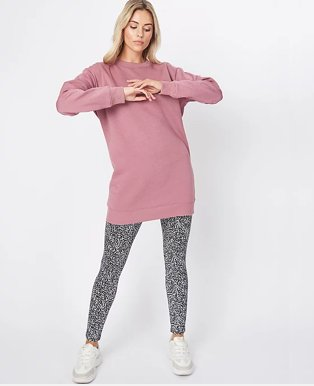 Woman with long blonde hair poses with hands together wearing pink longline sweatshirt, Noisy May black and white leopard print leggings and white pumps.