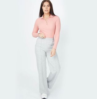 Woman with long brunette hair poses wearing peach cable knit zip neck jumper, grey marl pintuck wide leg trousers and white pumps.