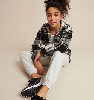 Girl sits on floor wearing a black, white and grey checkered shirt, grey joggers and black pumps.