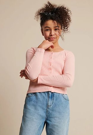 Girl poses wearing a pink button down cardigan and jeans.