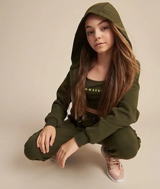 Girl crouches down wearing a khaki slogan top, hoodie and joggers.