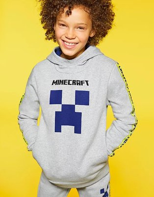 Child smiles wearing a grey Minecraft hoodie and joggers.