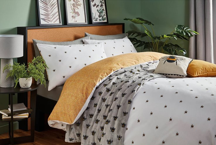 Double bed with white reversible bumblebee duvet set, yellow and bumblebee printed scatter cushions with floral wall art and artificial plants.