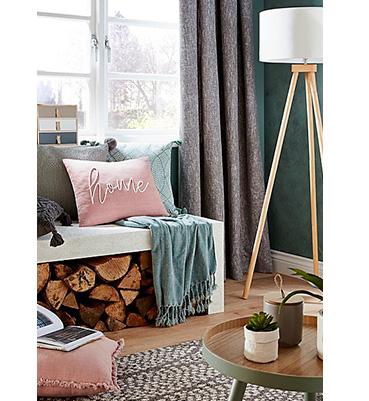 A window seat layered with cushions and a throw with a floor lamp on the side