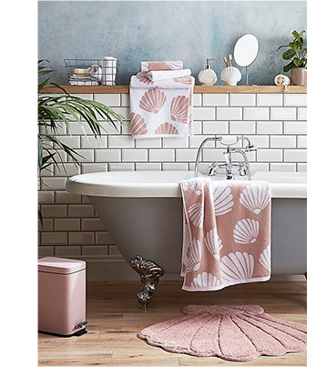 Grey bath with pink seashell towels and bathroom accessories
