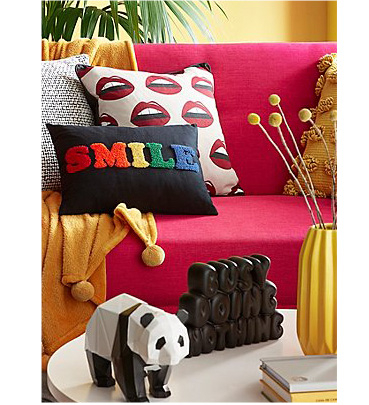 Pink sofa with printed cushions, a yellow throw and ornaments on a coffee table