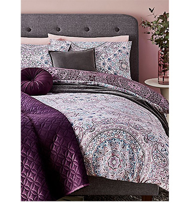 Purple printed duvet set with pillows and a purple throw