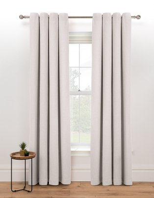Large white window features natural eyelet curtains hanging from bronze-tone curtain rail.