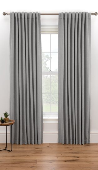 Large white window features grey eyelet curtains hanging from bronze-tone curtain rail.