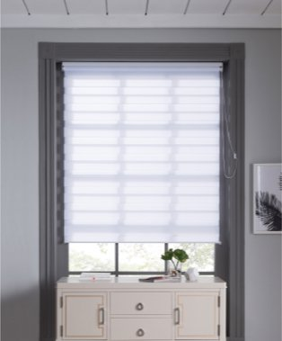 Large grey bathroom window features white blind with white storage unit below.