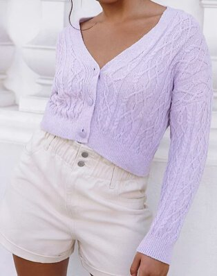 Woman poses wearing lilac patterned knit cropped cardigan and cream ruched waist shorts.