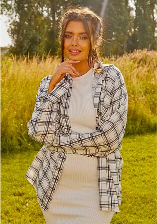 Woman poses in field wearing G21 white knit ribbed midi dress and G21 white oversized check shirt.