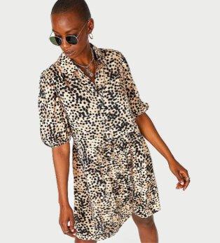 Woman poses wearing animal print balloon sleeve shirt dress and black circular sunglasses.
