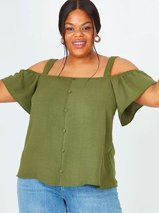 Woman poses smiling with arms raised wearing khaki cold shoulder top and blue mid-wash jeans.