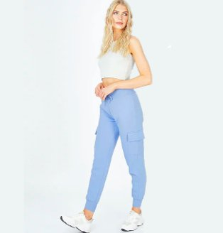 Woman poses taking one step forward wearing grey ribbed crop top, blue cargo joggers and white trainers.