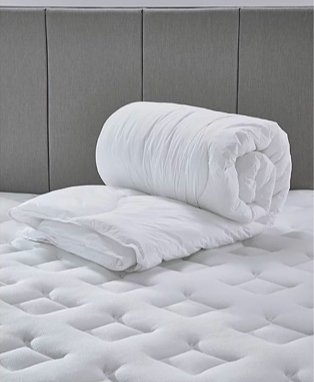 Luxury feels like down duvet rolled up on mattress topper.