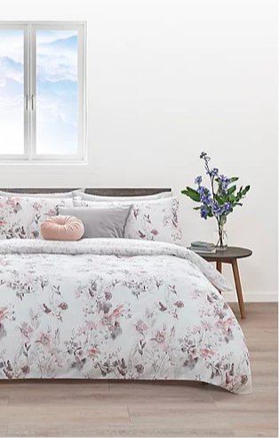 Double bed features floral duvet set with grey and pink scatter cushions with wooden side table and artificial plant.