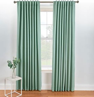 Large white window with green eyelet curtains on silver-tone curtain rail.