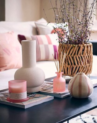 Coffee table features cream vase, artificial plant in wicker vase, pink candle, pink reed diffuser and pink and cream striped vase with cream sofa in the background.