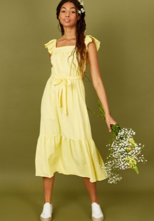 Woman poses holding bouquet of flowers wearing yellow tiered midi dress and white jute sole canvas shoes.