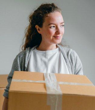 Woman poses wearing grey jumper holding brown cardboard box.
