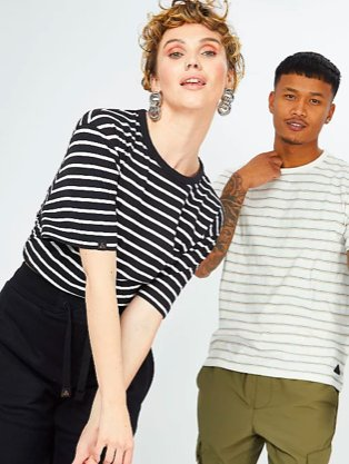 Woman poses with arms crossed wearing ADAPT unisex navy striped t-shirt and navy joggers. Man poses wearing ADAPT unisex white striped t-shirt and khaki cargo trousers.