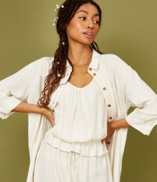 Woman poses with hands on hips wearing ivory textured stripe shirt over white cropped peplum vest top and cream linen blend stripe wide leg trousers.