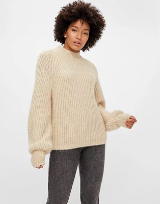 Woman poses wearing PIECES cream knit funnel neck jumper and grey acid wash skinny jeans.