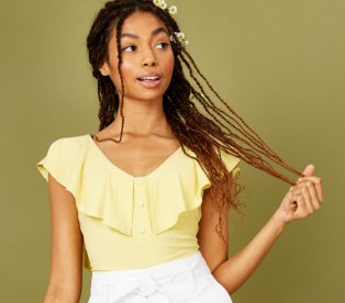 Woman poses holding tips of hair wearing yellow ruffled bodysuit and white belted shorts.