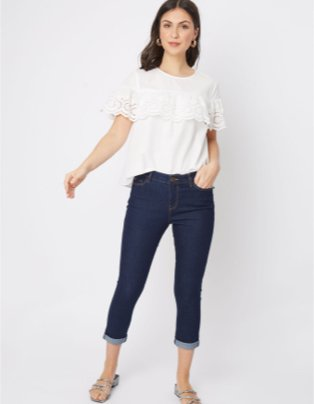 Woman poses wearing white frill trim t-shirt, dark wash mid-rise cropped jeans and silver strappy tie gladiator sandals.