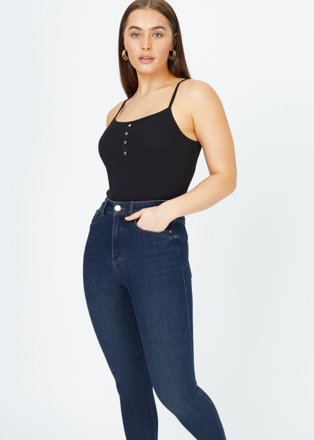 Woman poses with hand in pocket wearing black ribbed cami body tucked into dark-wash premium denim contour skinny jeans.