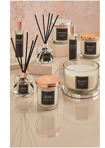 Numerous scented candles and votives and reed diffusers on a table