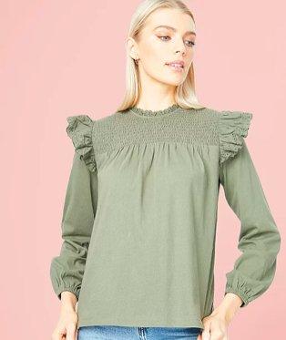 Woman poses wearing khaki frill trim long sleeve blouse.