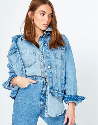 Woman poses with hand in pocket wearing denim shirt, light wash denim jacket and jeans.