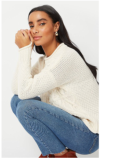 Woman crouching down wearing a cream knitted jumper and jeans
